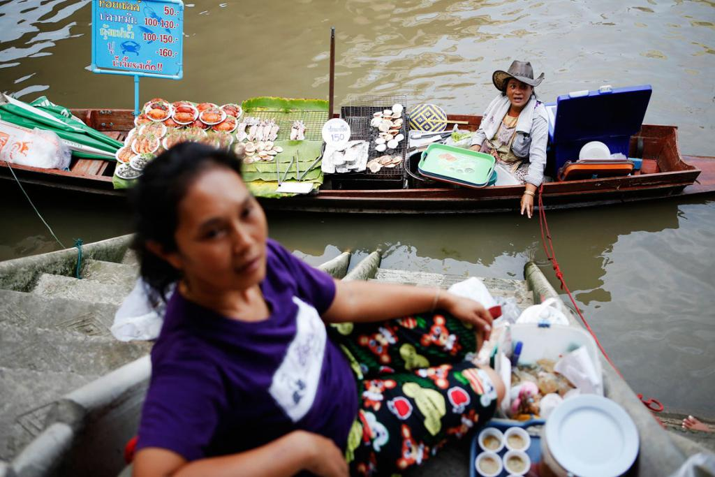 Vendors offer food from their small boats to people visiting the Amphawa floating market at Samut Songkhram province.