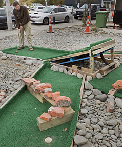 TEE BREAK: Dirk Weber, a volunteer with Gap Filler, tries his hand at a mini-golf hole which was made using recycled materials.