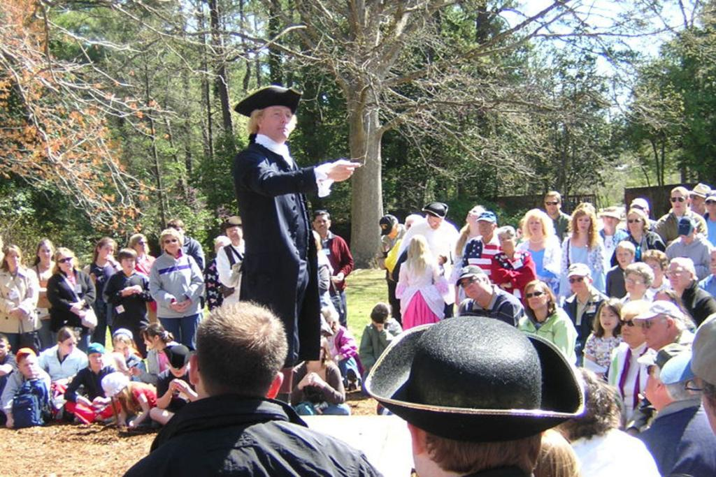 An actor portrays Thomas Jefferson giving a speech in the garden of the Governor's Palace at Colonial Williamsburg.