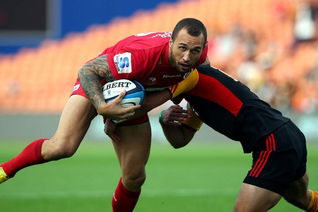 The Reds' Quade Cooper is tackled by the Chiefs' Aaron Cruden during their clash in Hamilton.