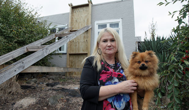 SOLO BATTLE: Two years on from her husband's death, earthquake widow Julie Caldwell, pictured with dog Chance, is struggling to cope  in a house that is still broken.