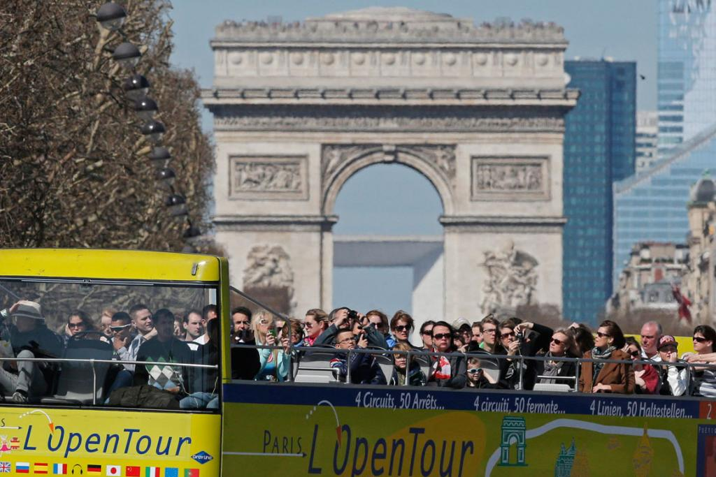 Tourists ride in an open-air double-decker bus down the Champs Elysees avenue in front of Paris landmark, the Arc de Triomphe, during a mild and sunny spring day in Paris.