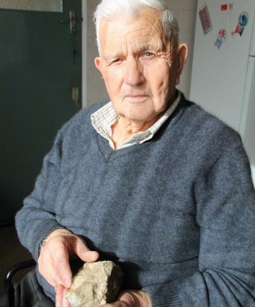 Pacific War veteran George Vernon holds some of the scheelite rock used as steel for guns.