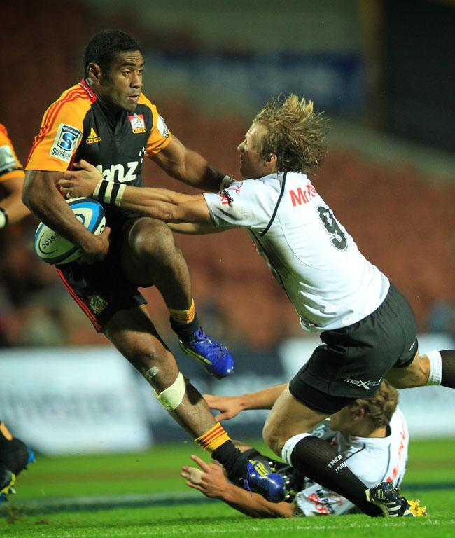 Asaeli Tikoirotuma attempts to break through a Sharks tackle.