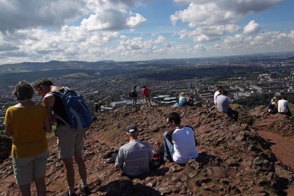 Tourists relax and take in the view over Edinburgh after climbing to the summit of Arthur's Seat during in the Edinburgh Fringe Festival.