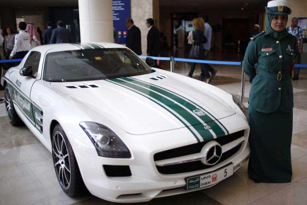 A police officer stands near a Mercedes SLS AMG car used by Dubai police, during the Arabian Travel Market exhibition in Dubai.