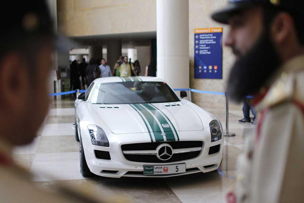 Police officers stand near a Mercedes SLS AMG car used by Dubai police, during the Arabian Travel Market exhibition in Dubai.