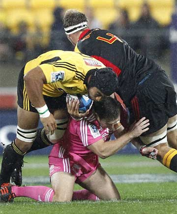 REF UNDER SIEGE: Referee Lourens van der Merwe gets stuck between Hurricanes loose forward Victor Vito (left) and Chiefs lock Craig Clarke during their Super Rugby match in Wellington.