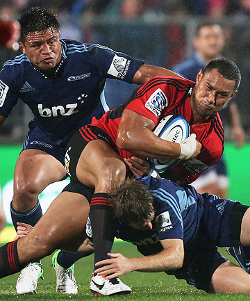 SOGGY NIGHT: Robbie Fruean of the Crusaders is tackled by Chris Noakes with Keven Mealamu of the Blues.
