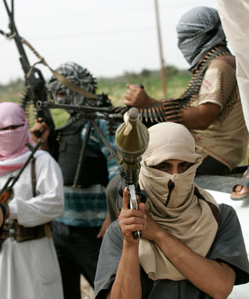 Tribal men hold weapons as they patrol a road 100 km west of Baghdad.