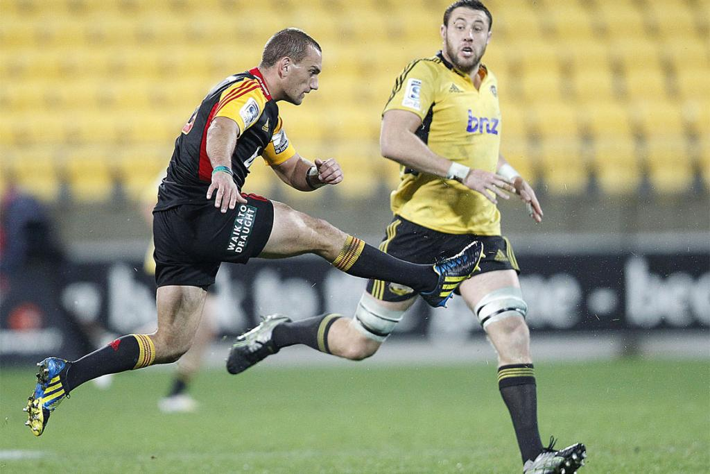 Aaron Cruden gets a kick away under pressure from Hurricanes lock Ben May.