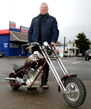 Second Time Around store assistant Maurice Burgess poses with the mini-chopper motorcycle outside the store in Picton