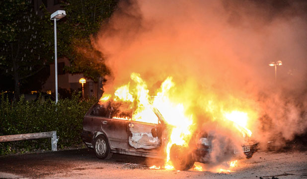 A car set on fire burns, following riots in the Stockholm suburb of Kista.