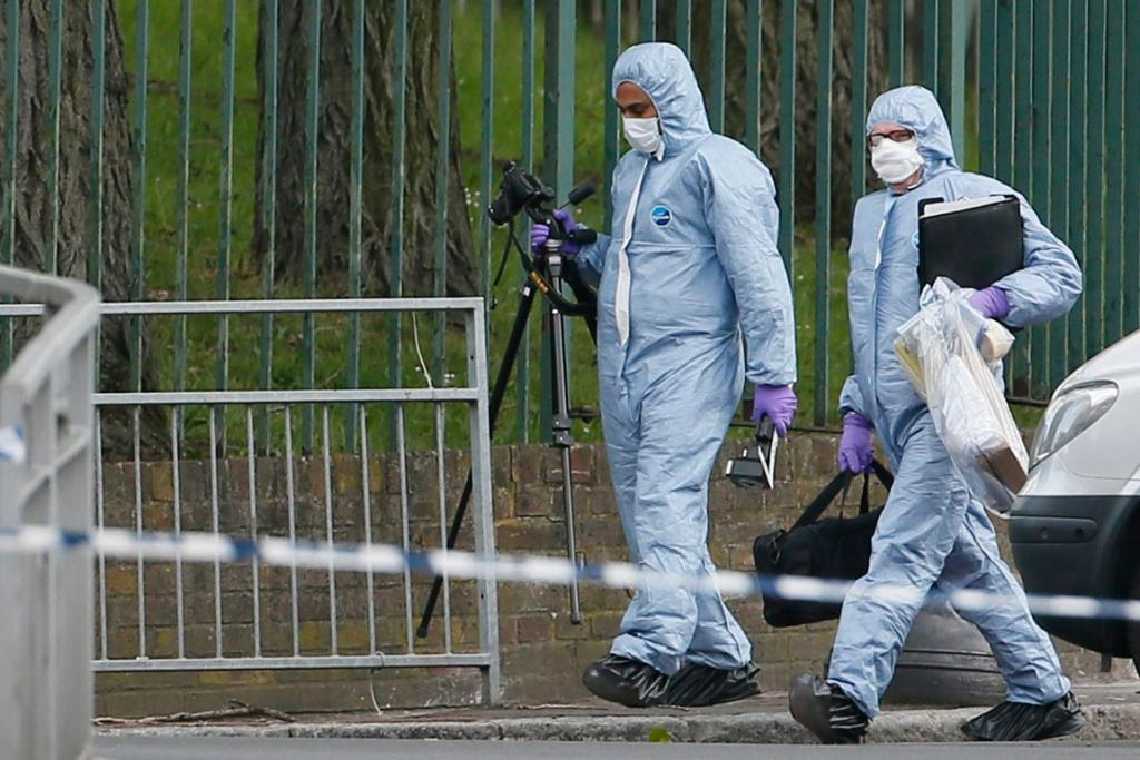 Forensic police work at the scene where a man was hacked to death.