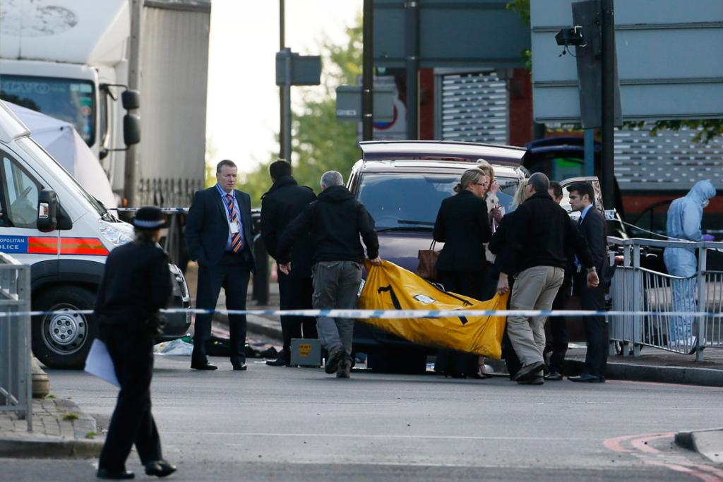 Police carry equipment at the scene after the attack.