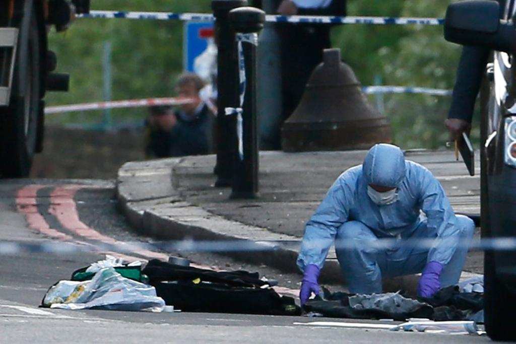 A forensic police officer works at the scene.