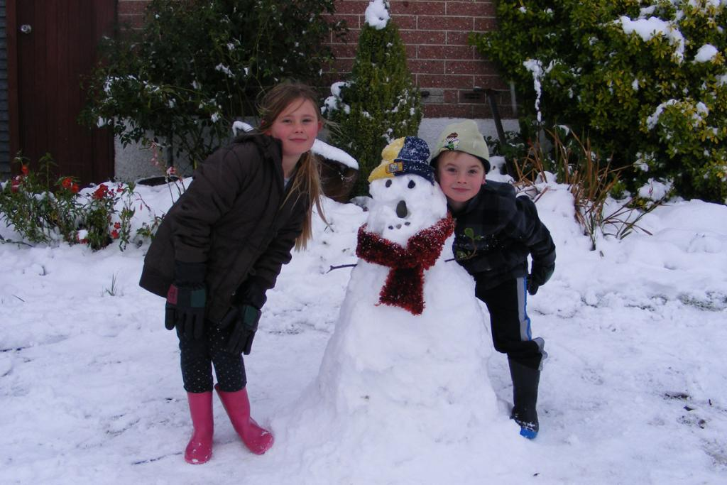 Pyper, 7, and Lucas, 5, make the most of the cold snap to build a snowman at Brockville Park.