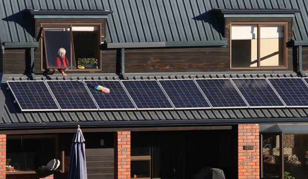 SUSTAINABLE ENERGY: Sue Matthews dusts her solar panels. Sue Matthews dusts her solar panels.