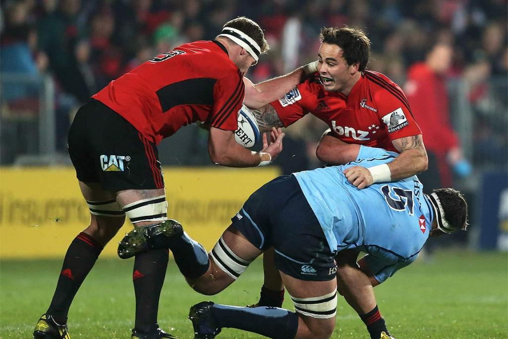Zac Guildford of the Crusaders passes the ball back to Kieran Read under pressure from Waratah Kane Douglas.