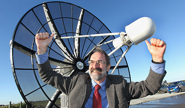 SKY HIGH: Venture Southland engineer Robin McNeill with the satellite dish that tracked the rocket as it passed over Southland.
