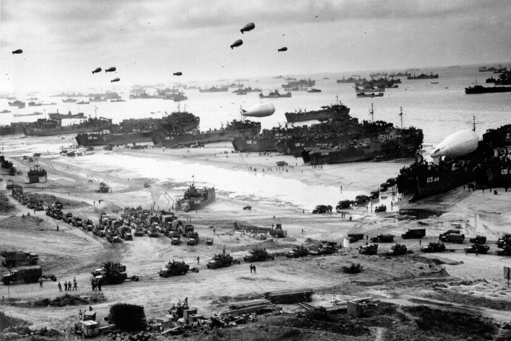 LSTs (Landing Ship Tanks), landing vehicles, and cargo are pictured on a Normandy beach in this June 1944.