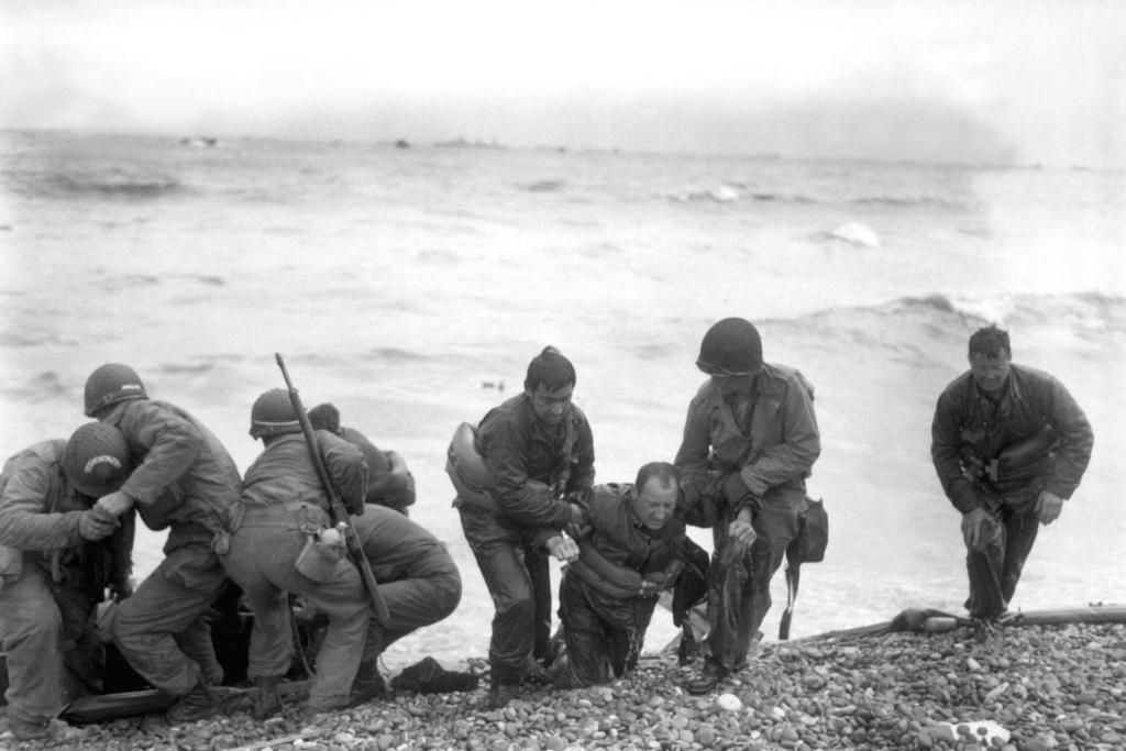 Members of an American landing party lend helping hands to others whose landing craft was sunk by enemy action off the coast of France.  These survivors in the photo reached Utah Beach, near Cherbourg, by using a life raft.