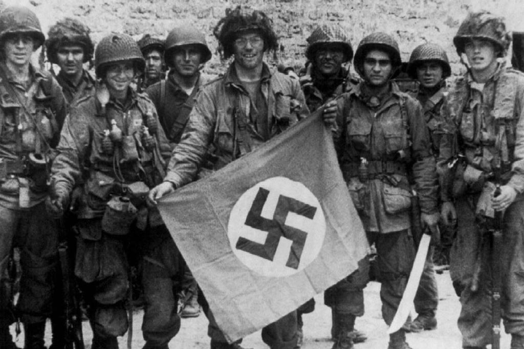 American paratroopers display a Nazi flag captured in a village assault, shortly after the Normandy landings of June 6, 1944.