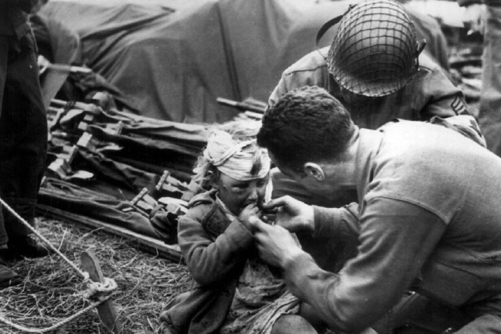 US medical corpsmen give candy to a wounded French child during the D-Day invasion at a beachead dressing station in June 1944.
