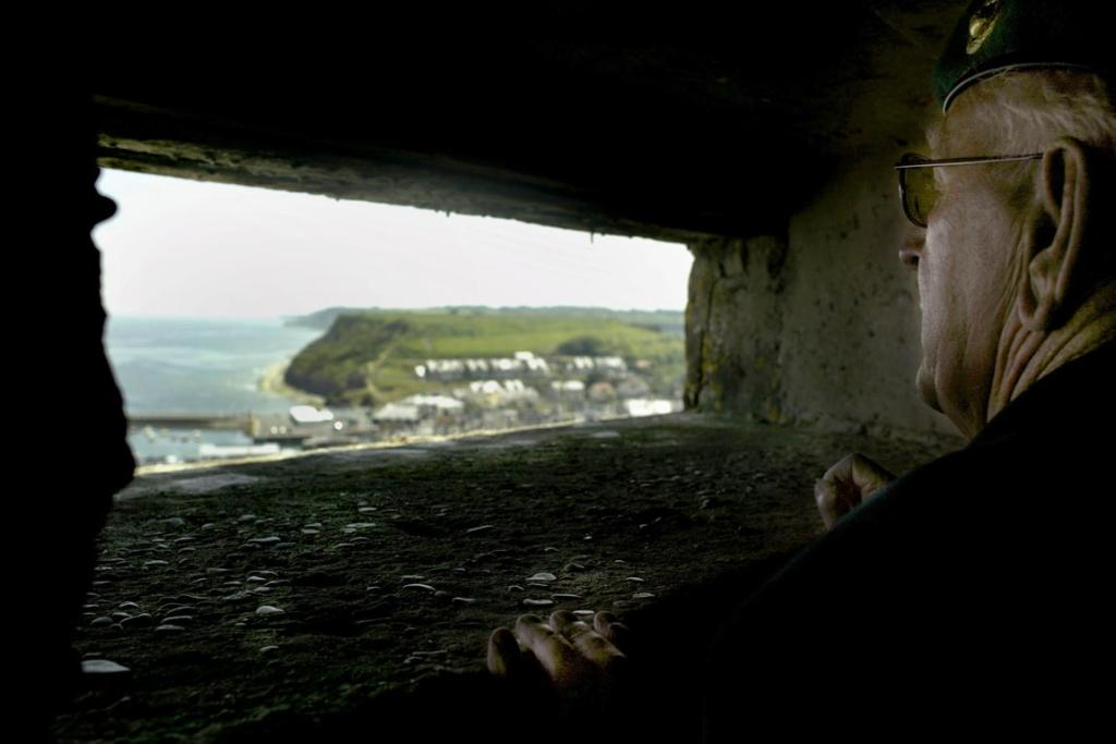 British Royal Marine veteran George Amos looks out from a German bunker at Port-en-Bessin Huppain, Normandy, June 7, 2004.  Amos was held prisoner in the bunker, yet later led the surrender of the position to allied forces.