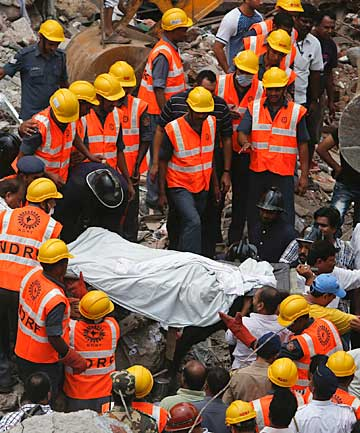 DEADLY COLLAPSE: Rescue workers recover a body from the debris at the site of a collapsed residential building in central Mumbai.