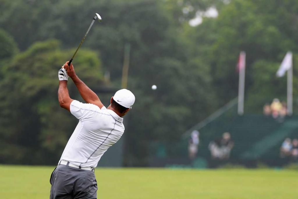 Tiger Woods plays a shot through the rain to the green during a practice round.