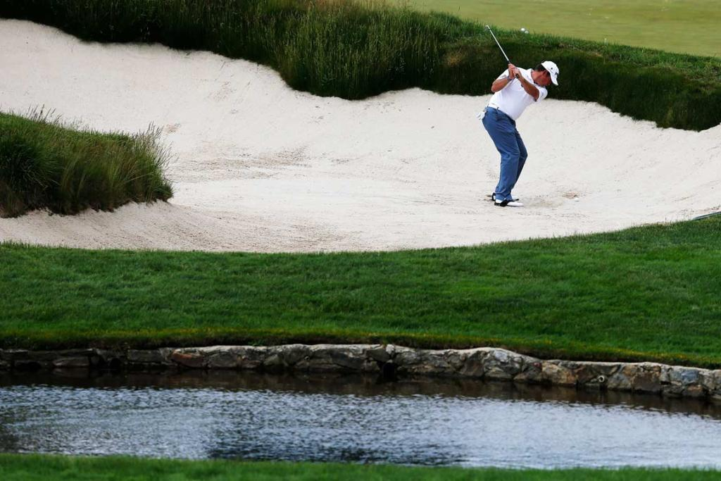 Lee Westwood of England plays out of a bunker during a practice round at Merion.