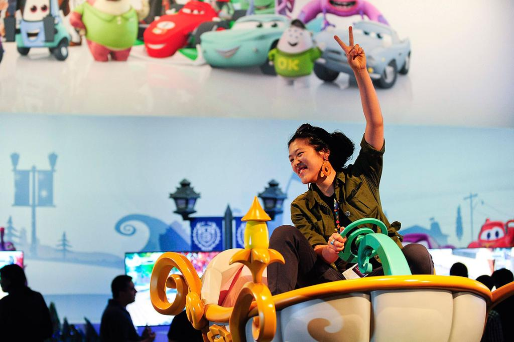 Yun Dai  tries out the updated full size of Cinderella's carriage at the Disney Booth at E3.
