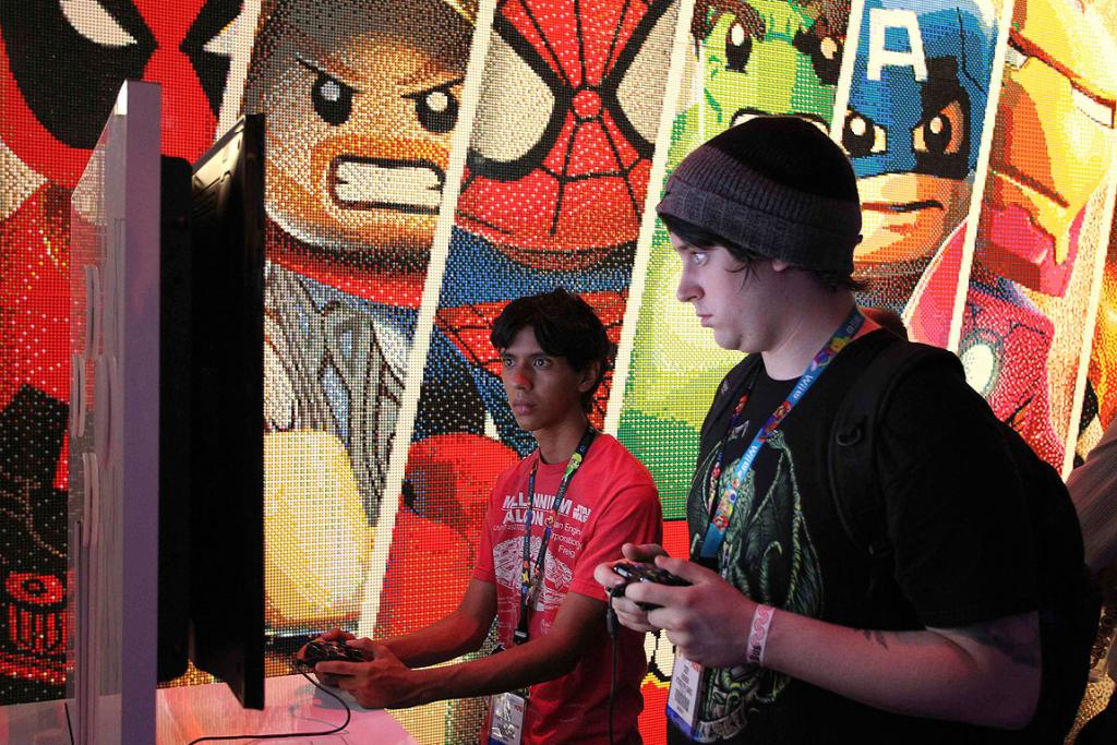 Attendees try out LEGO'S Marvel SuperHeroes game at the Lego exhibit during E3.