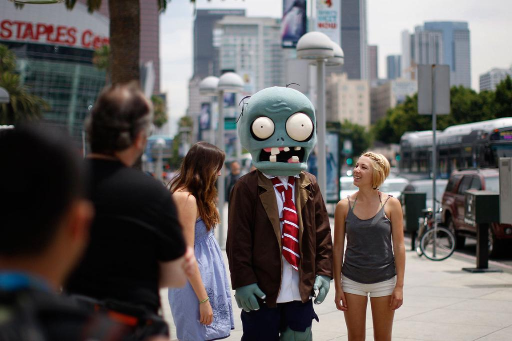 A person dressed as a zombie in the Zombies vs Plants 2 game walks down the street to E3.