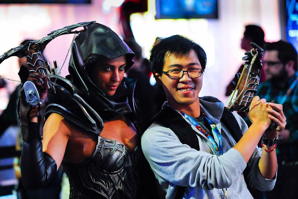 A visitor poses with actor reprised as a game character during E3 in Los Angeles.