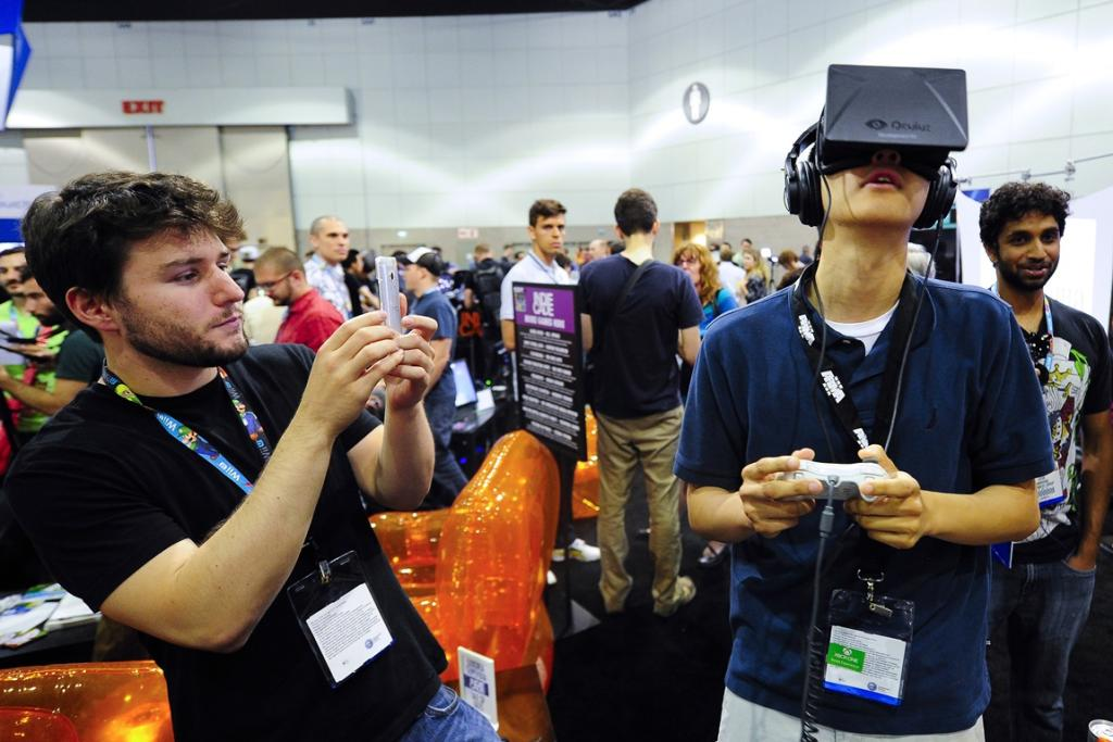 Rectal software designer Julian Kantor (L) takes a picture of Jonathan Feng (R) as he uses the Oculus Rift virtual reality headset to experience his program.