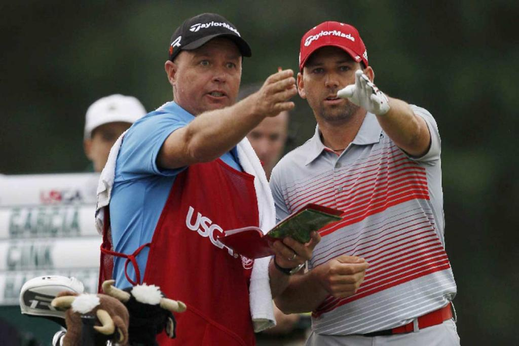 Sergio Garcia discusses a shot with his caddie during the first round.