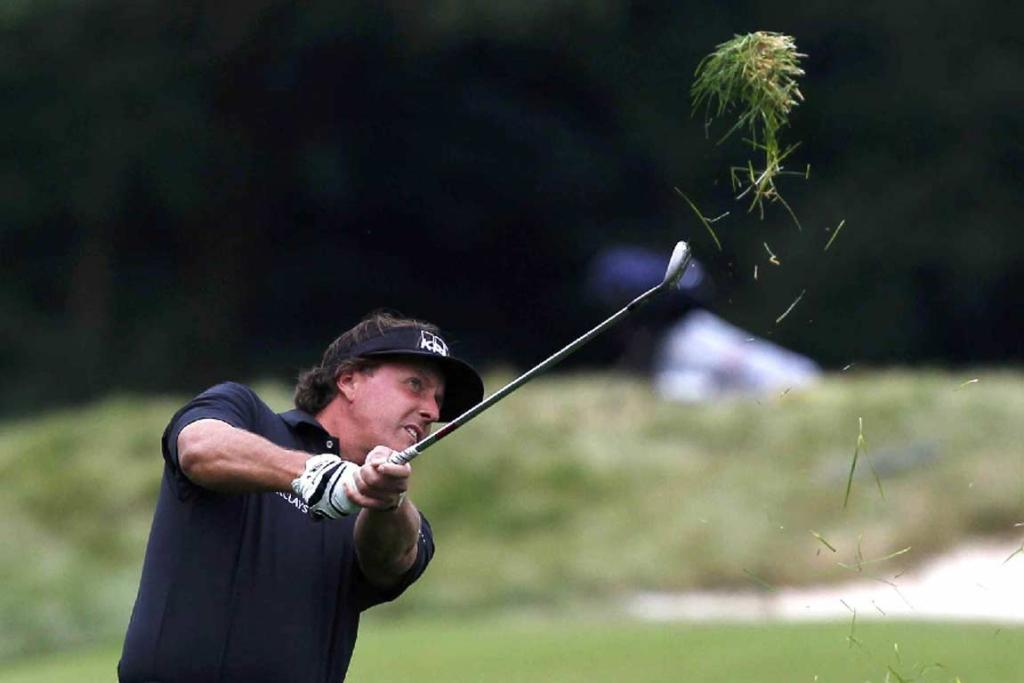 Phil Mickelson takes a chunk of grass out with his second shot from the 12th fairway.