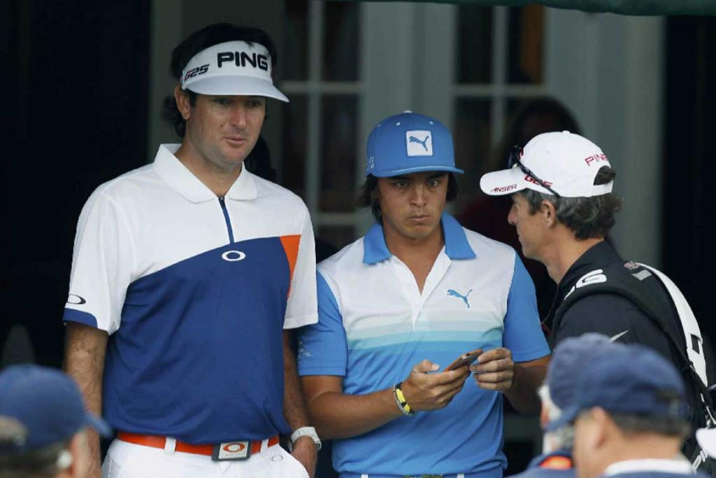 Bubba Watson (left) and Rickie Fowler wait at the clubhouse during the weather delay.