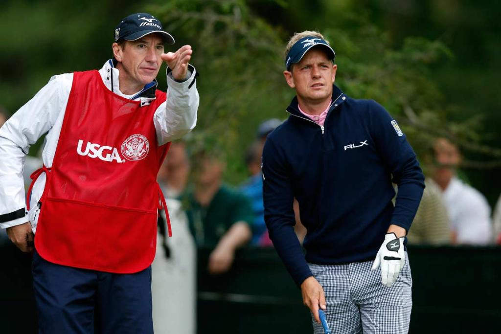 Luke Donald receives some instructions from his caddie John McLaren as he finishes his first round at Merion.