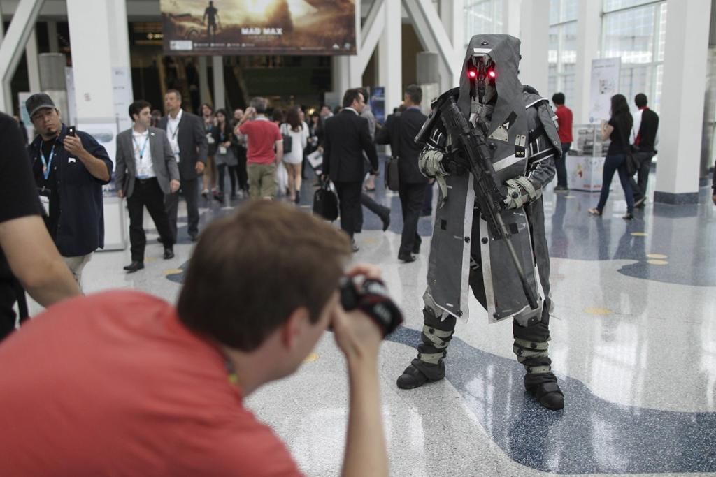 An attendee photographs a Helghast sniper character from the PS4 game Killzone: Shadow Fall.