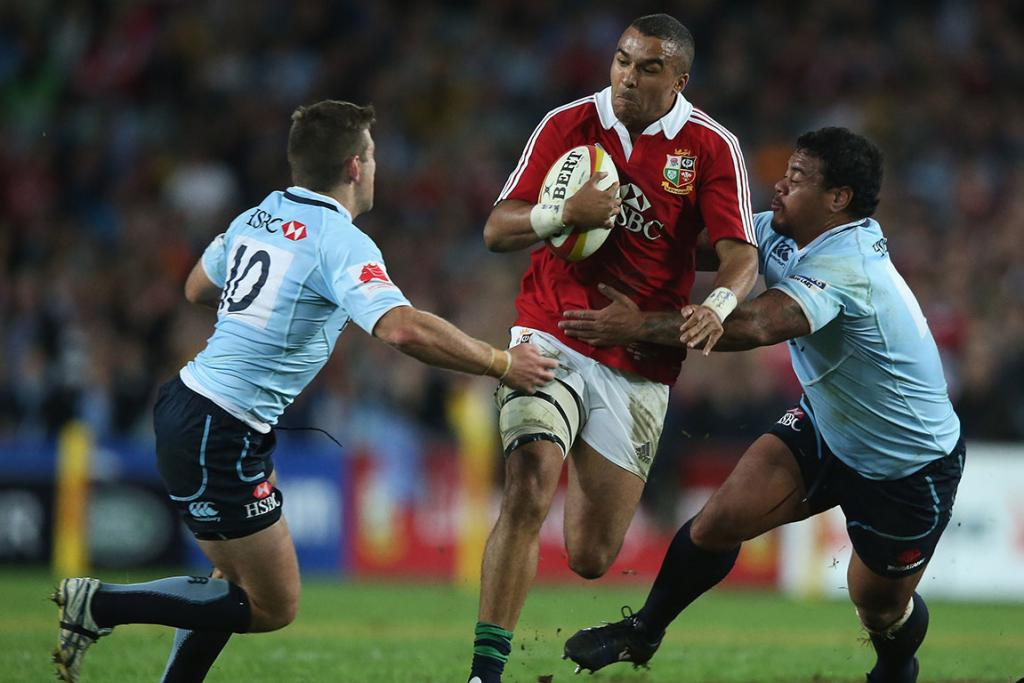 Simon Zebo of the Lions is tackled by Bernard Foley (L) and John Ulugia during the match between the NSW Waratahs and the British & Irish Lions.