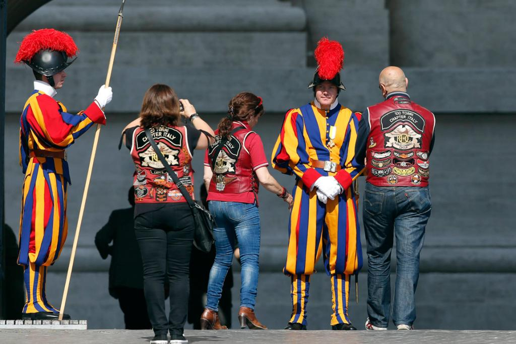 Harley-Davidson bikers pose for a picture beside a Swiss Guard before the mass.