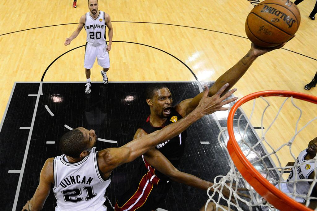 Chris Bosh of the Heat drives on the Spurs' Tim Duncan.