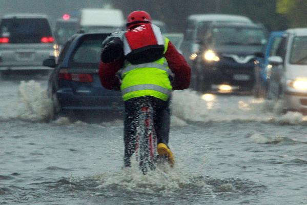 Cyclist on flooded intersection