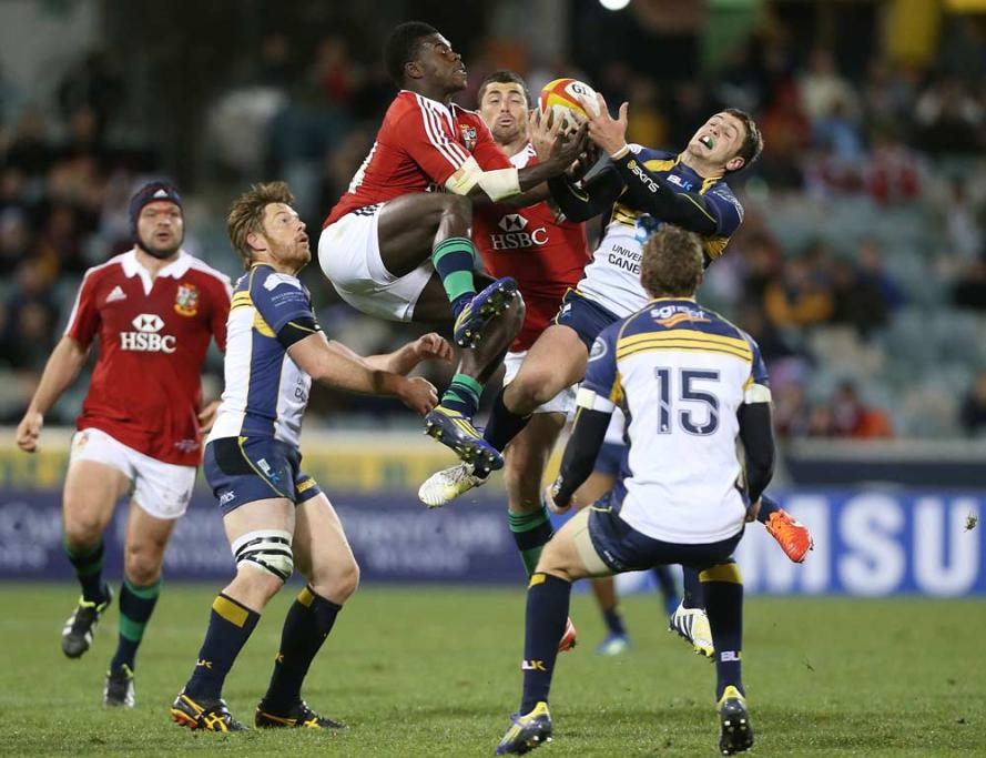 British & Irish Lions wing Christian Wade leaps for a high-ball against the Brumbies' Ian Prior during their tour match at Canberra Stadium.