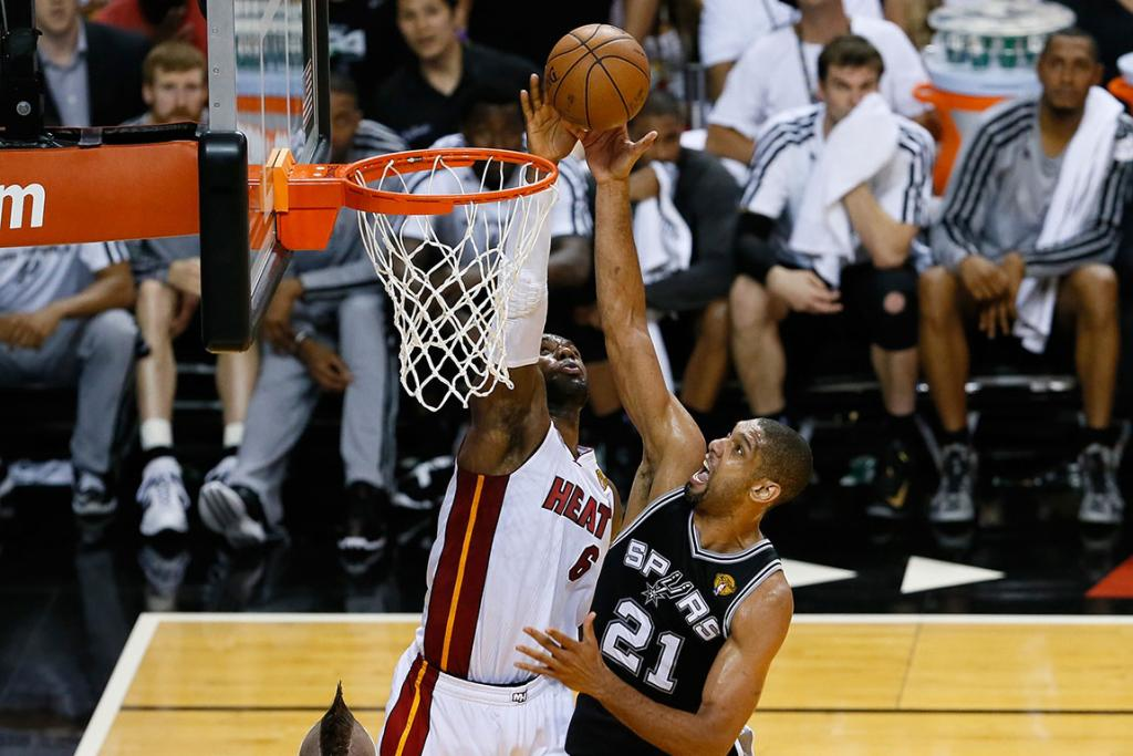LeBron James of the Heat attempts a clock on the spurs' Tim Duncan.