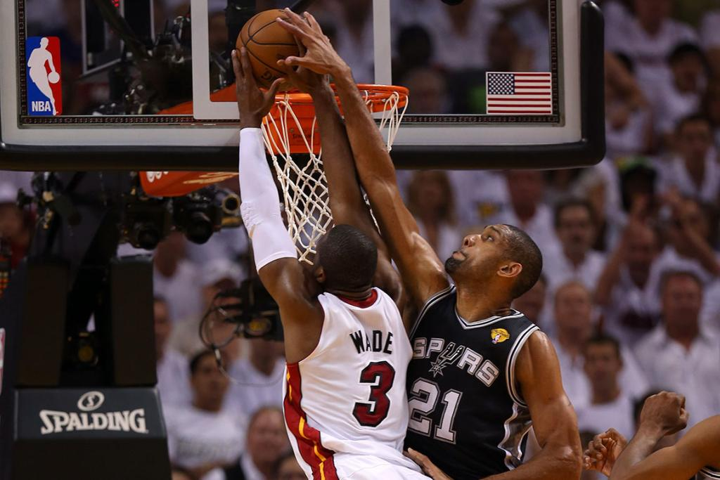 Tim Duncan goes for a block on a Dwyane Wade slam.
