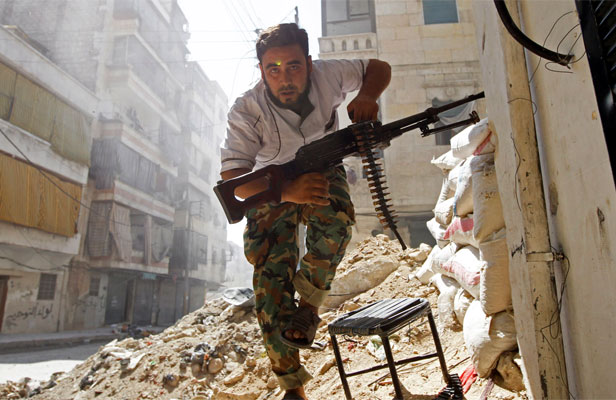 A Free Syrian Army fighter takes cover during clashes with Syrian Army in the Salaheddine neighbourhood of central Aleppo in 2012.